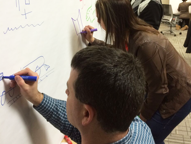 Individuals working on adding graphics and text to a mapped-out idea structure on a large whiteboard