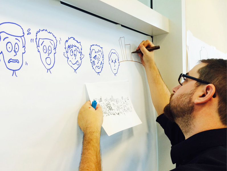 Graphic facilitator drawing cartoon faces with various expressions on a whiteboard